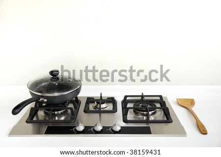 A kitchen hob with a saucepan and a wooden ladle. - stock photo