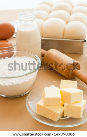 A kitchen scene with the ingredients for baking and bread dough in tin ready to bake. - stock photo