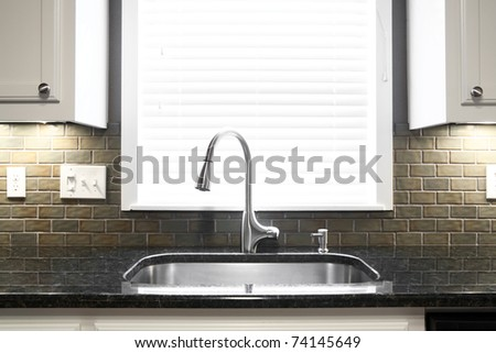 A kitchen sink and window centered in a kitchen - stock photo