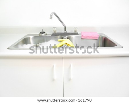 A kitchen sink with cleaning supplies. - stock photo