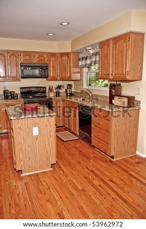 A kitchen with hardwood floors in a residential home.