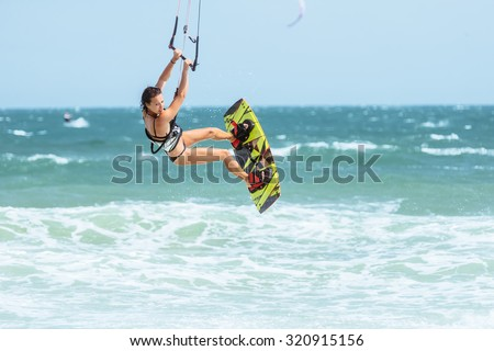 A kite surfer rides the waves. - stock photo
