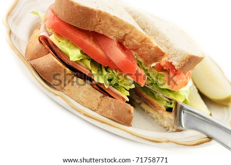 A knife cutting through a ham, cheese and bologna sandwich, diagonal viewpoint with white copy space - stock photo