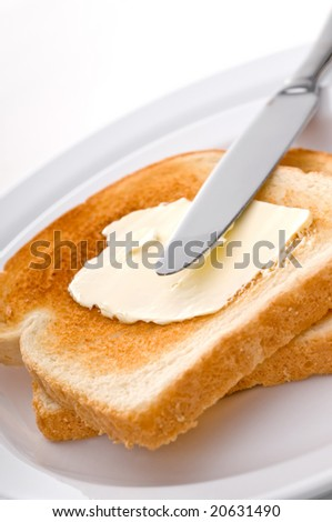 A knife spreading butter on toast on a white plate - stock photo