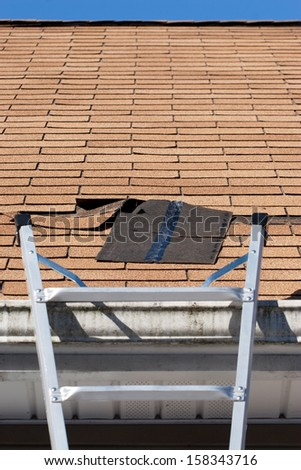 A ladder set up to repair damaged roof shingles.  A section was blown off after a storm with high winds causing a potential leak. - stock photo