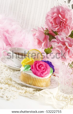 A ladies tea party with a delicious decorated cupcake and fresh roses - stock photo
