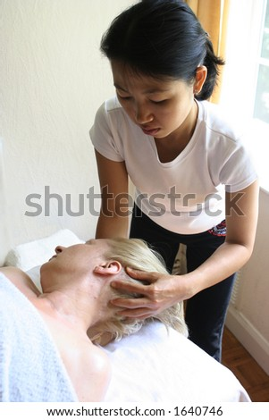 A lady masseur giving a head massage to her client . ( Suitable for spa image )