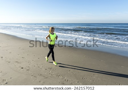 A lady running on the beach - stock photo