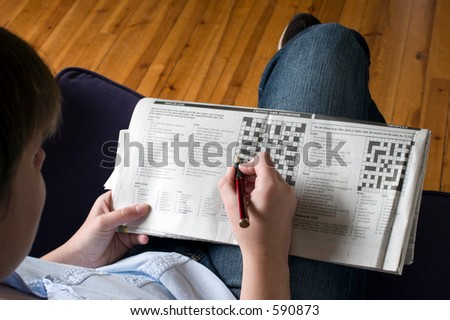 A lady sitting on a sofa doing the crossword casually on her knee.