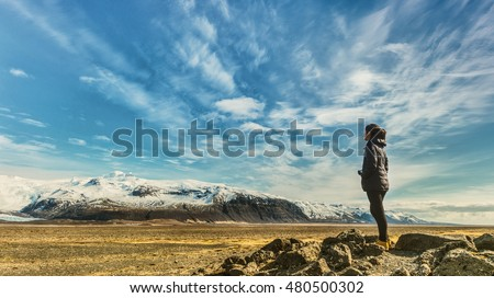 A lady traveller standing on rocks along the road is looking at the view of mountain range covered by snow in Iceland during the end of summer.