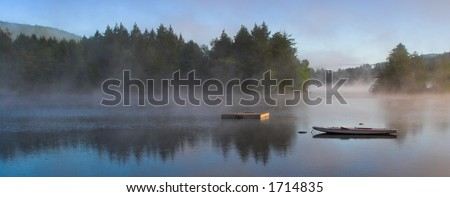 A lake in the early morning with rising fog. Panorama format. - stock photo