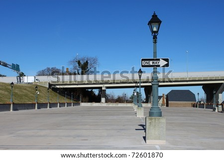 A Lamp lined concrete parking lot at the foot of a bridge in Yorktown Virginia and a one way sign going in the direction of travel for the bridge traffic with room for your text. - stock photo