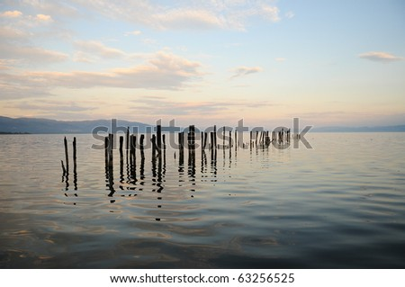 A landing jetty at a calm lake on a misty autumn sunset 