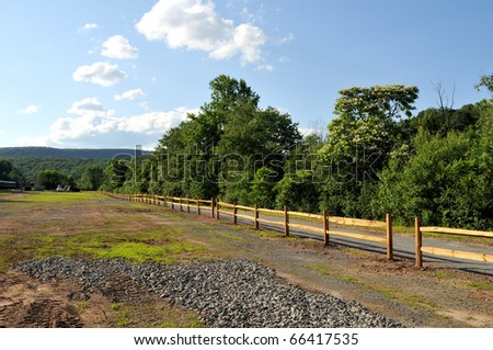 A landscape depicting a wooden fence along a rural road with mountains and blue sky with white clouds, at Jim Thorpe, Pocono Mountains, New York, USA.