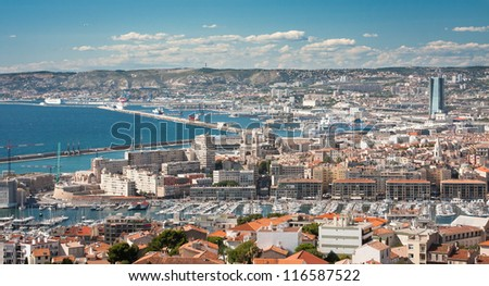 A landscape of Marseille from above with the see and mountains and white clouds in the background