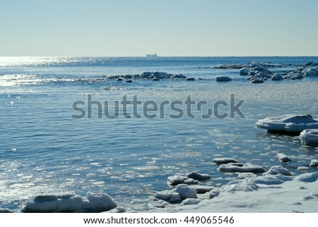 A landscape on winter sea, water, stones, ice and ship on horizon. - stock photo