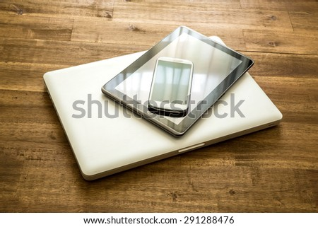 A Laptop computer, a Tablet PC and a Smartphone on a wooden Desktop.