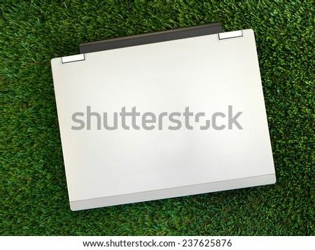 A laptop computer on artificial grass - stock photo