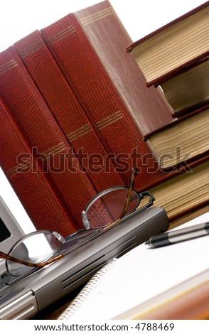 A laptop computer with books all around. Working on a paper. - stock photo