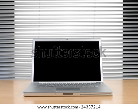 A laptop on a table at a modern office. - stock photo