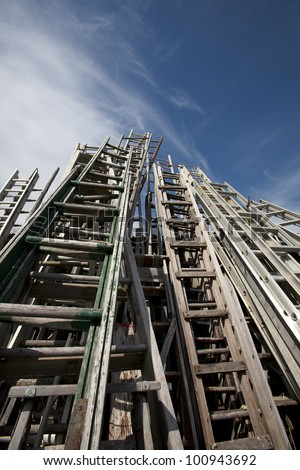A large amount of antique and old ladders reaching up to the sky. - stock photo
