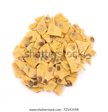 A large amount of peanut brittle candy on a white background. - stock photo