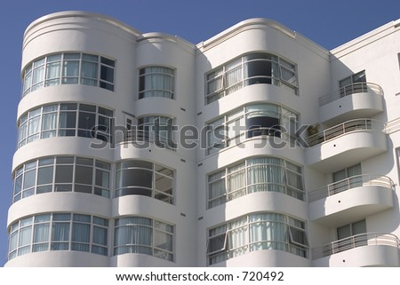 A large art deco apartment building displays it's face of curved windows and balcony's.