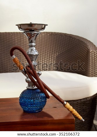 A large, blue, luxury glass hookah sits on a table in the sunshine at an outdoor hookah lounge with a rattan couch.  - stock photo
