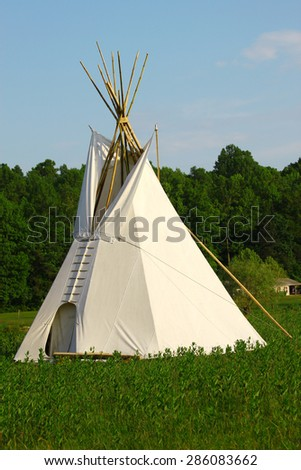 A large canvas teepee out in the middle of a brush filled field on a clear gorgeous summer day - stock photo