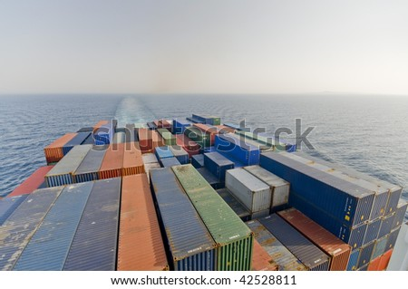 a large container vessel ship and the horizon, no logos in this picture - stock photo