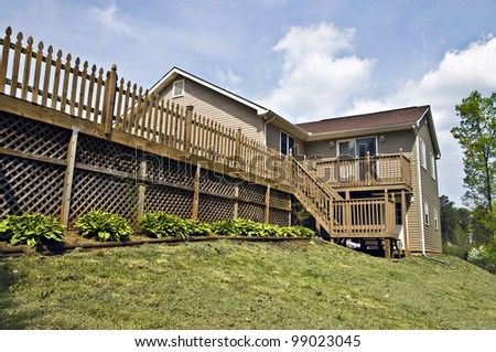 A large deck design on the back of a house.