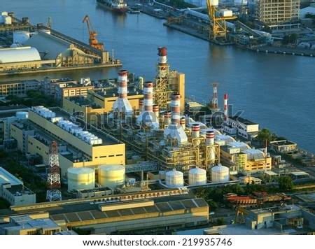 A large factory and industrial complex situated on the waterfront by the harbor  - stock photo