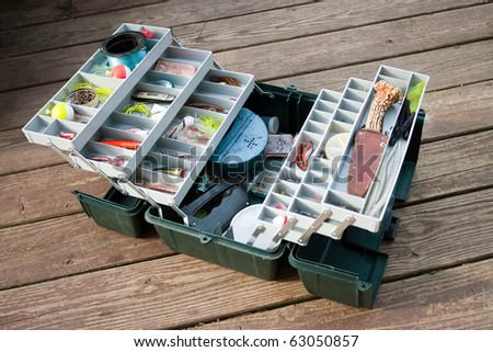 A large fisherman's tackle box fully stocked with lures and gear for fishing. - stock photo