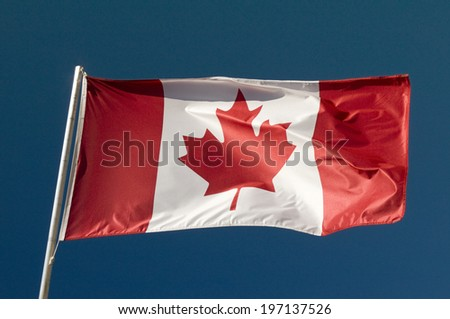 A large flag of Canada on a flagpole. - stock photo