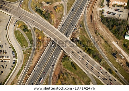 A large freeway interchange with an overpass near parking lots. - stock photo