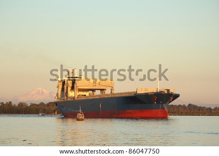 A large freighter moves down the Fraser River at sunset making it's way through the fishing fleet that are fishing for salmon. Richmond, British Columbia, Canada near Vancouver. - stock photo