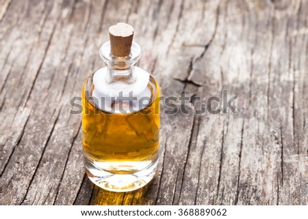 A large glass bottle of essential oil on a wooden floor - stock photo