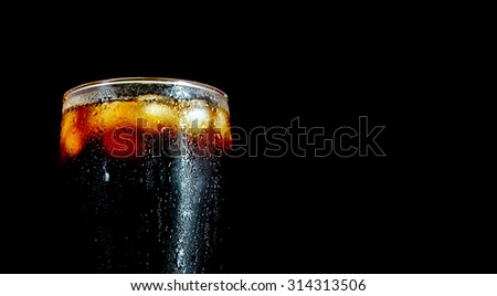 a large glass of cola closeup with ice cubes isolated on black background - stock photo