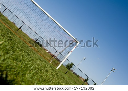 A large grassy field with a soccer net. - stock photo