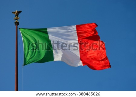 A large green, white and red national flag of Italy blowing in the wind in front of a blue sky background.