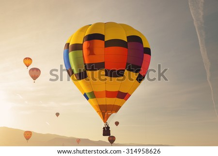 a large hot air balloon flies over the sky during sunrise or sunset with a bright sun glare across the sky