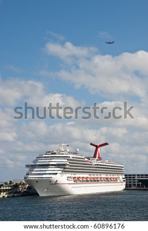 A large luxury cruise ship in a harbor with a commerical airline flying overhead
