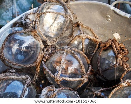 A large metal bucket filled with clear glass fishing floats all wrapped in rope netting. - stock photo