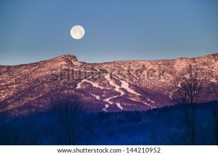 A large moon rising over Mt. Mansfield at sunrise in Stowe, Vermont, USA - stock photo