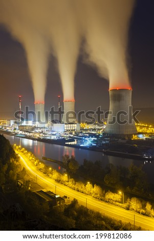 A large nuclear power station by a river at night with lots of steam
