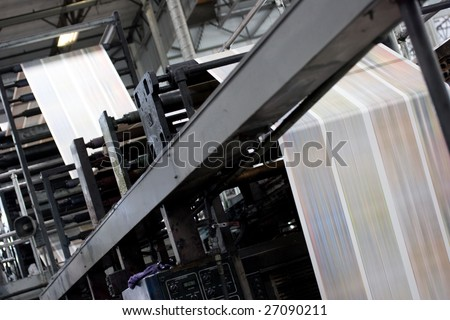 A large offset printing press running a long roll off paper over its rollers at high speed. - stock photo
