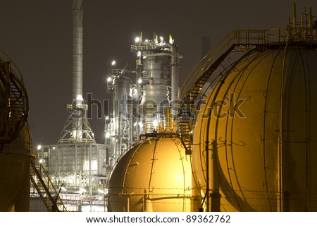 A large oil-refinery plant with gas storage tanks - stock photo