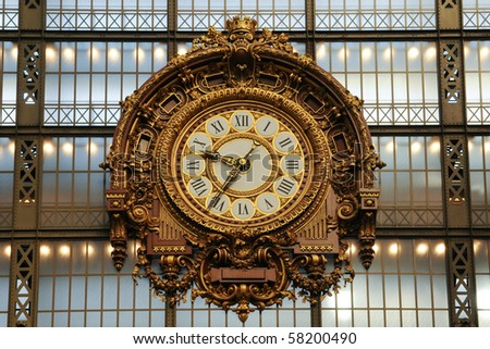 A large old decorated antique clock at an old train station. The clock face has Roman numerals. - stock photo