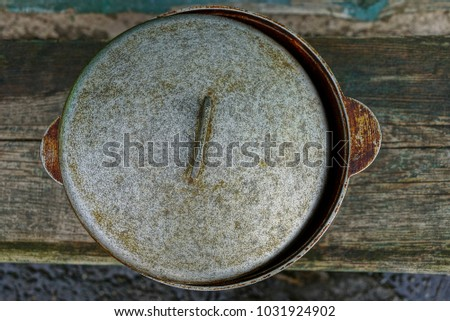 A large old saucepan with a gray lid on the table
