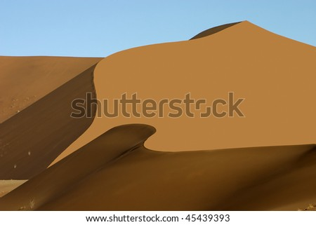 A large orange sand dune with wave like shadows to the bottom and side against a light blue sky - stock photo